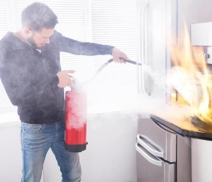 Fires can happen anytime, call SERVPRO of Bartlett/ Cordova anytime! Image of man spraying fire extinguisher in kitchen.